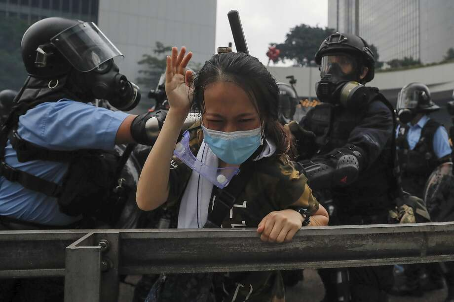 A demonstrator shields herself from police during a protest outside the Legislative Council in Hong Kong. Photo: Kin Cheung / Associated Press
