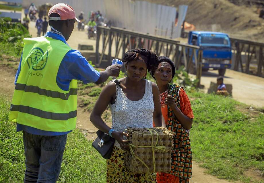 A health worker takes people's temperatures as they cross between Kasindi, Congo, and Bwera, Uganda. Photo: Al-hadji Kudra Maliro / Associated Press