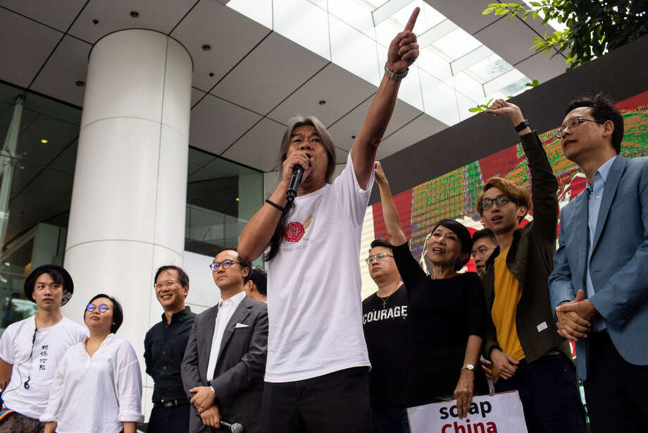 """Leung """"Long Hair"""" Kwok-hung, legislator and chairman of the League of Social Democrats, center, gestures as he addresses the media during a protest against a proposed extradition law in Hong Kong, China, on June 12, 2019. Photo: Bloomberg Photo By Eduardo Leal / Bloomberg"""