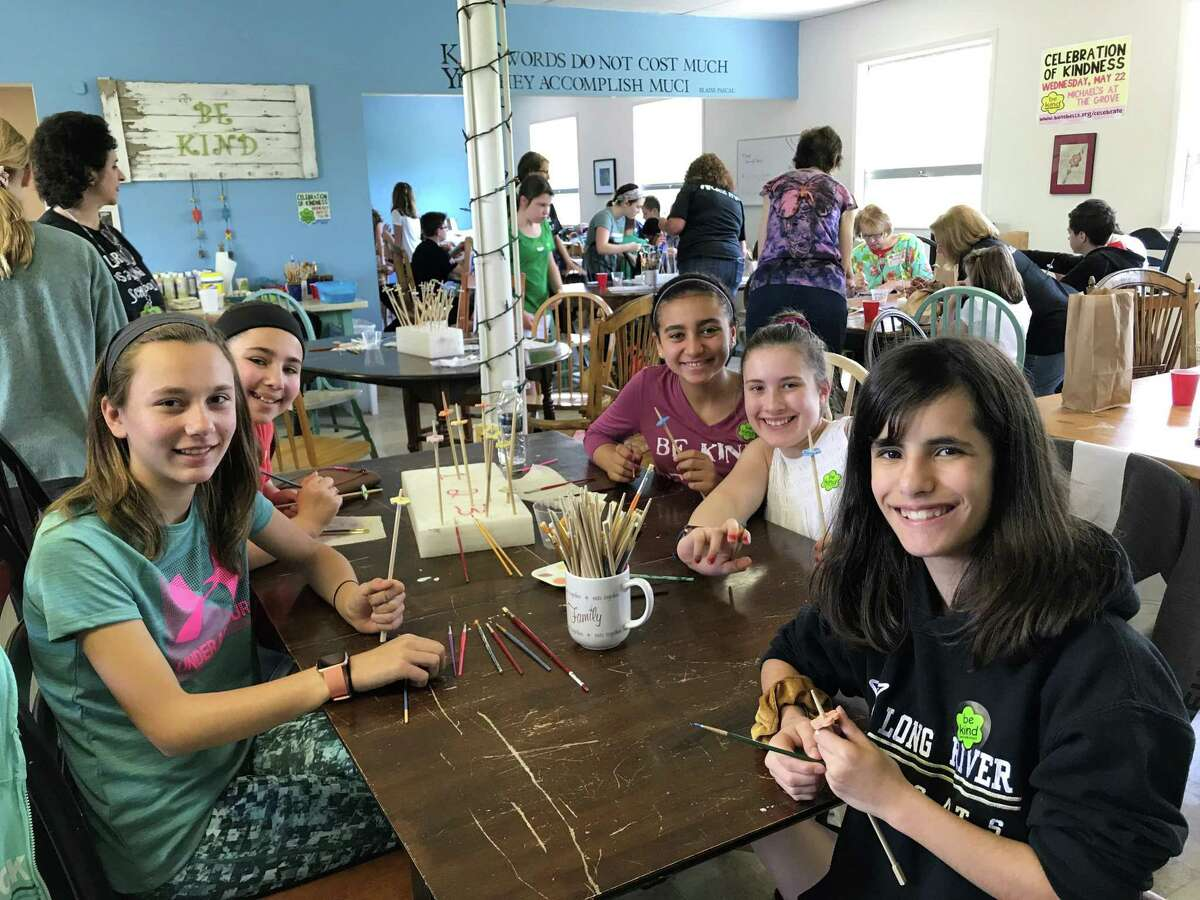 A group of seventh-graders from Long River Middle School paint Kindness Coins.