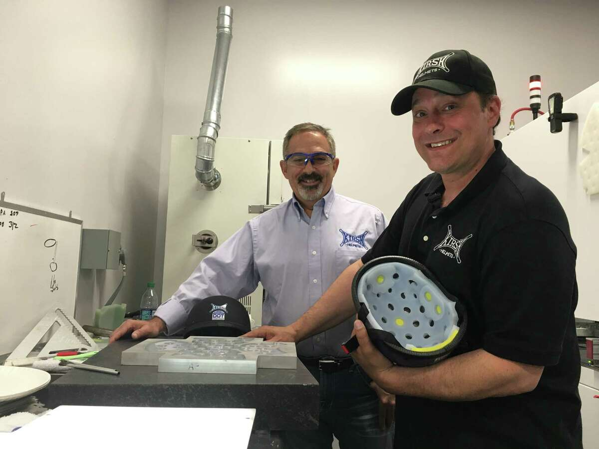 Donald DeVito and Jason Kirshon stand inside the Specialty Silicon Products manufacturing facility in Ballston Spa on June 12. The company partners with several Capital Region-based companies to produce their high-end motorcycle helmets.