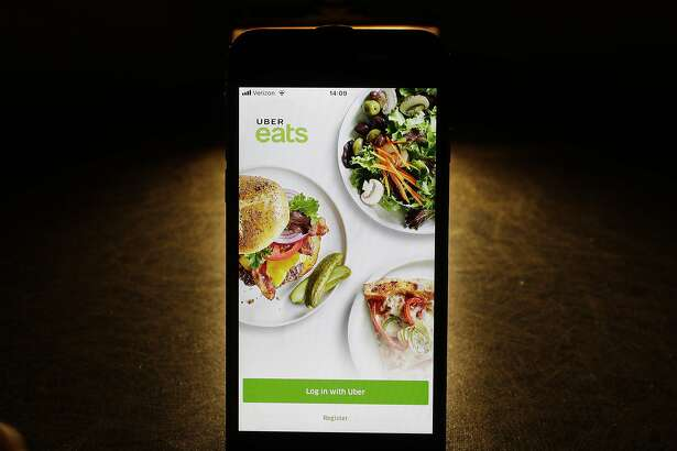 FILE - In this Feb. 20, 2018, file photo shows the Uber Eats app on an iPhone in Chicago. Uber is testing restaurant food deliveries by drone. The company's Uber Eats unit began the tests in San Diego with McDonald's and plans to expand to other restaurants later this year. (AP Photo/Charles Rex Arbogast, File)