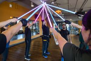 Participants at the SF academy of LudoSport lightsaber combat academy class hold their lightsabers together at the end of their class at Studiomix in San Francisco.