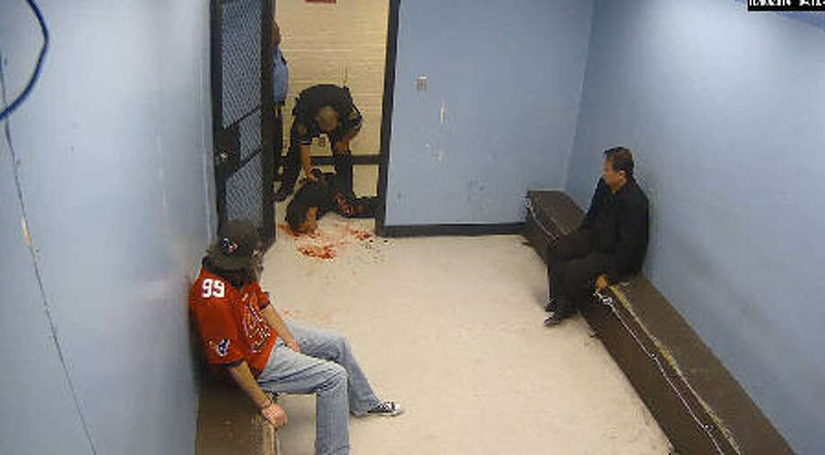A frame grab of footage from a city jail downtown in 2014  shows Officer Salvador R. Corral, of Houston Police Department, holding a man's head against a jail cell door, bloodying his face.