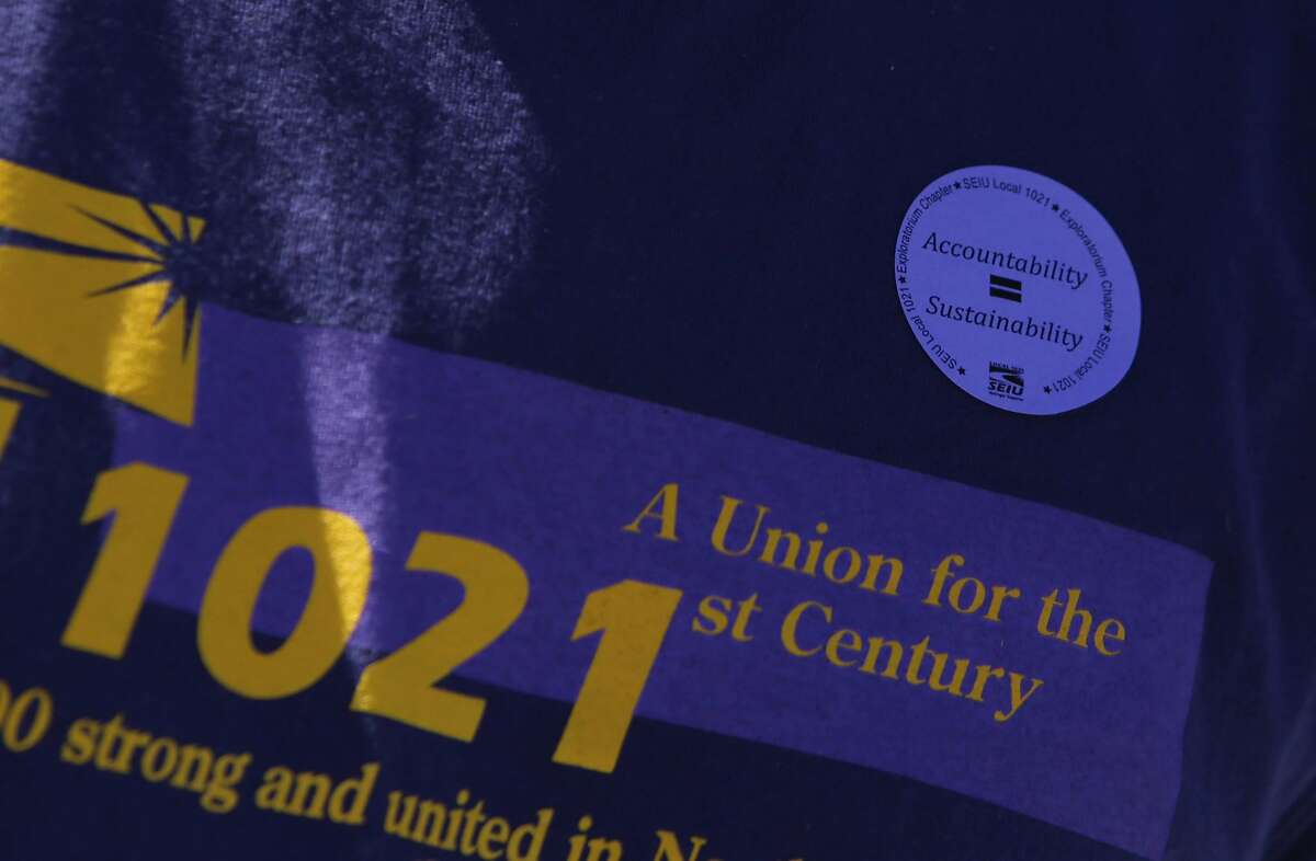 One attendee wears a SEIU Local 1021 shirt with a sticker supporting the Exploratorium Chapter SEIU Local 1021 during the rally at Pier 15 on Thursday, October 1, 2015 in San Francisco, Calif.
