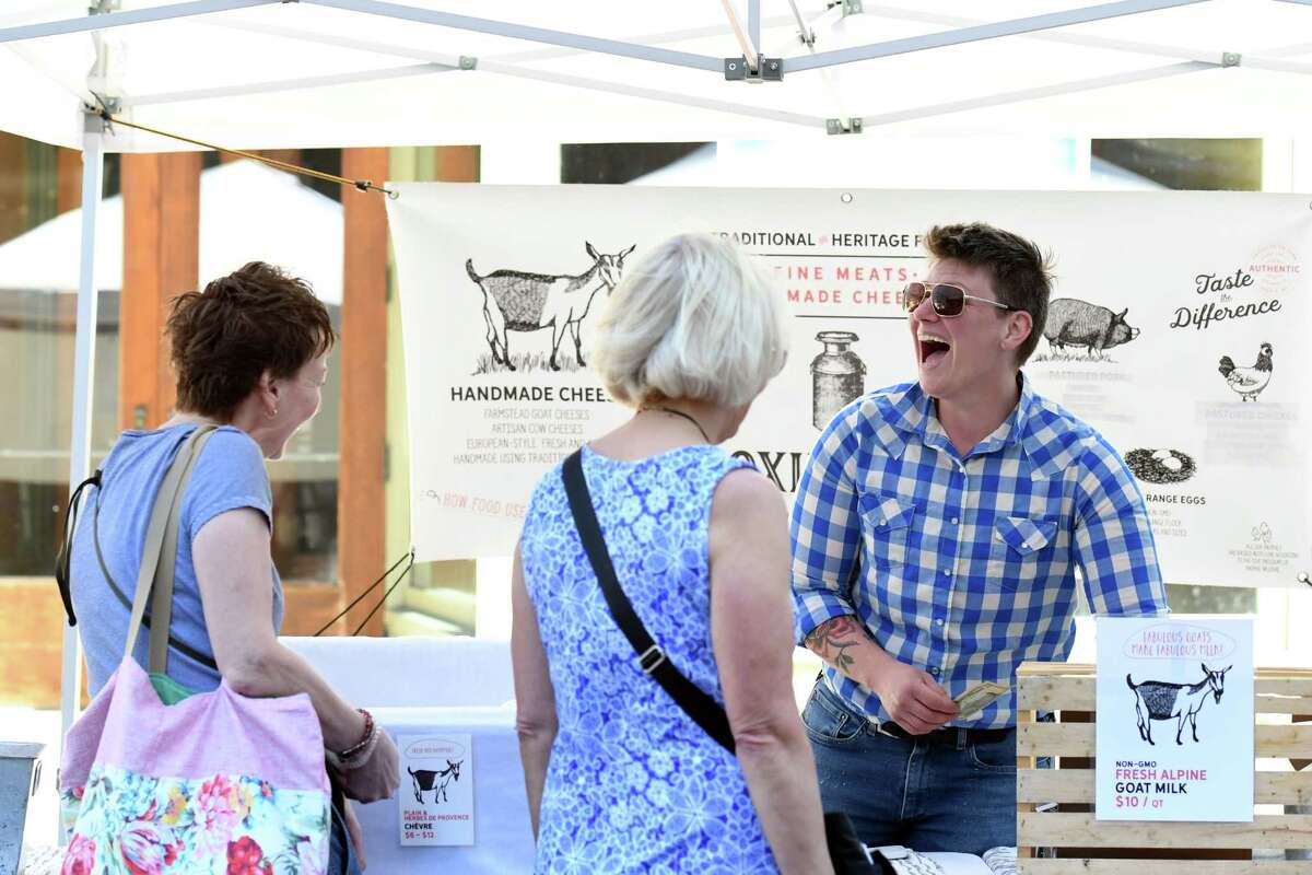 Moxie Ridge Creamery owner Lee Hennessy chats with customers Barbara Charlebois, left, and Jackie Bogardus at his booth on Saturday, June 8, 2019 at the Troy Farmers Market in Troy, NY. (Phoebe Sheehan/Times Union)