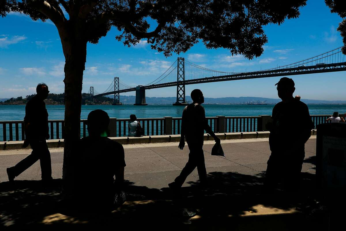 People walk along the Embarcadero in San Francisco, California, on Wednesday, June 12, 2019.