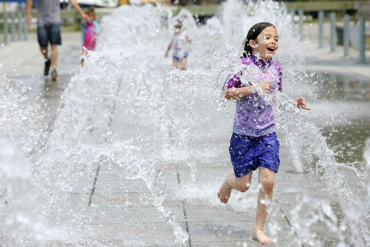 Seven-year-old Adia runs through the water fountain at Lake Union Park to stay cool as temperatures reached a record high of 90 degrees in the Seattle area according to the National Weather Service, Wednesday, June 12, 2019.