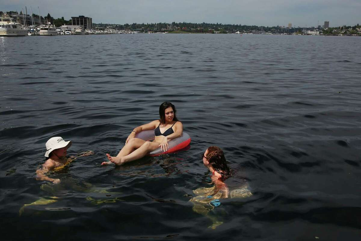 SPU students Asia Cayetano, left, Symone Tran, center, and Mallie Donohoe cool off in Lake Union as temperatures reached a record high of 90 degrees in the Seattle area according to the National Weather Service, Wednesday, June 12, 2019.