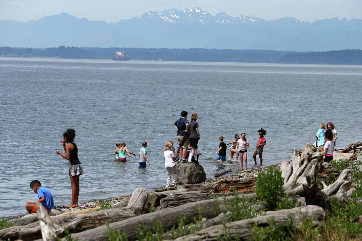 Kids play in the water off Lincoln Park as temperatures reached a record high of 90 degrees in the Seattle area according to the National Weather Service, Wednesday, June 12, 2019.