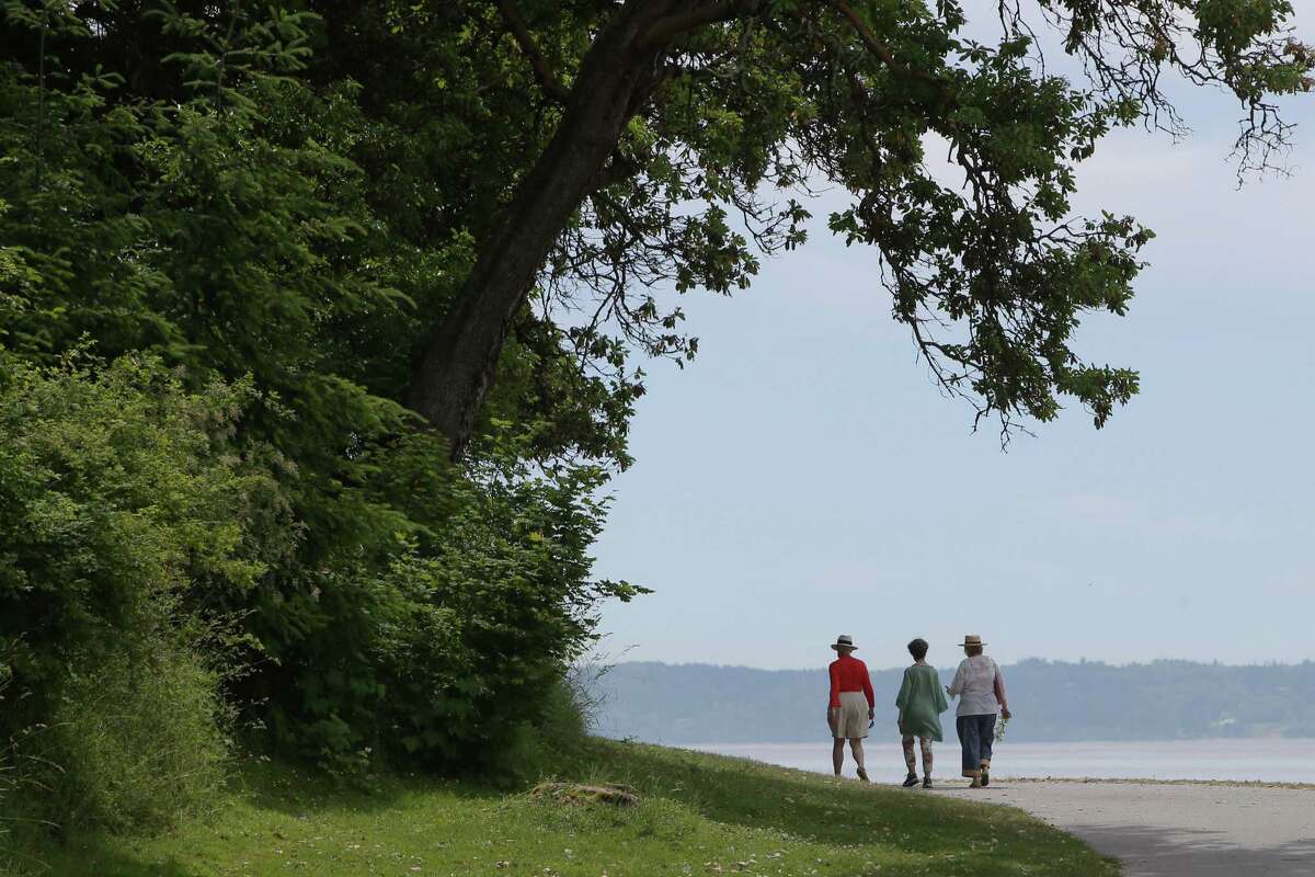 Three women walk along the water at Lincoln Park as temperatures reached a record high of 90 degrees in the Seattle area according to the National Weather Service, Wednesday, June 12, 2019.