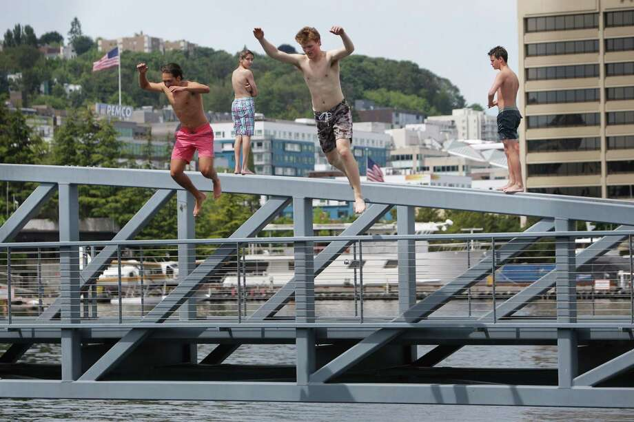 Claton Seibel and Roan Gerrald jump off the pedestrian bridge at Lake Union Park as temperatures reached a record high of 90 degrees in the Seattle area according to the National Weather Service, Wednesday, June 12, 2019. Photo: Genna Martin, SEATTLEPI / GENNA MARTIN