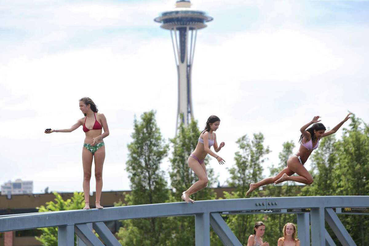 Girls jump from the pedestrian bridge into Lake Union as temperatures reached a record high of 90 degrees in the Seattle area according to the National Weather Service, Wednesday, June 12, 2019.