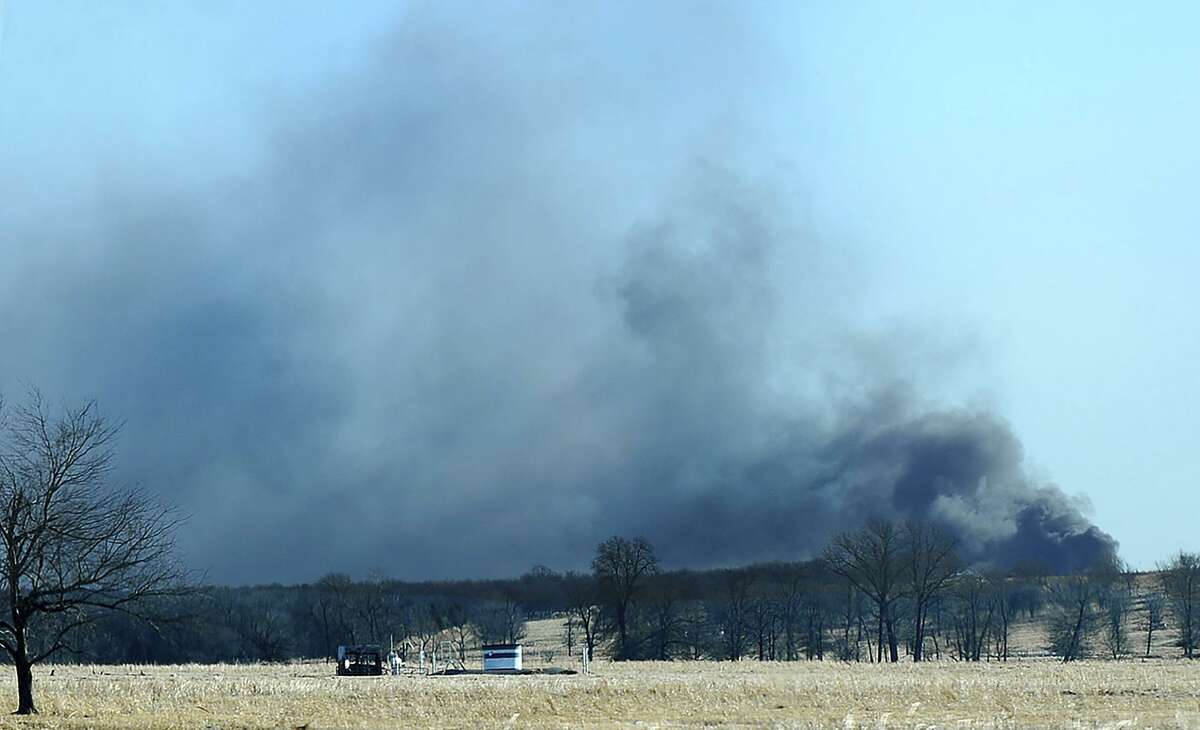FILE - In this Monday, Jan. 22, 2018, file photo, smoke billows from the site of a gas well fire near Quinton, Okla. A federal report says the explosion and fire that killed five workers at the southeastern Oklahoma natural gas well in 2018 was caused by the failure of blowout prevention devices and other factors. (Kevin Harvison/The McAlester News-Capital via AP, File)