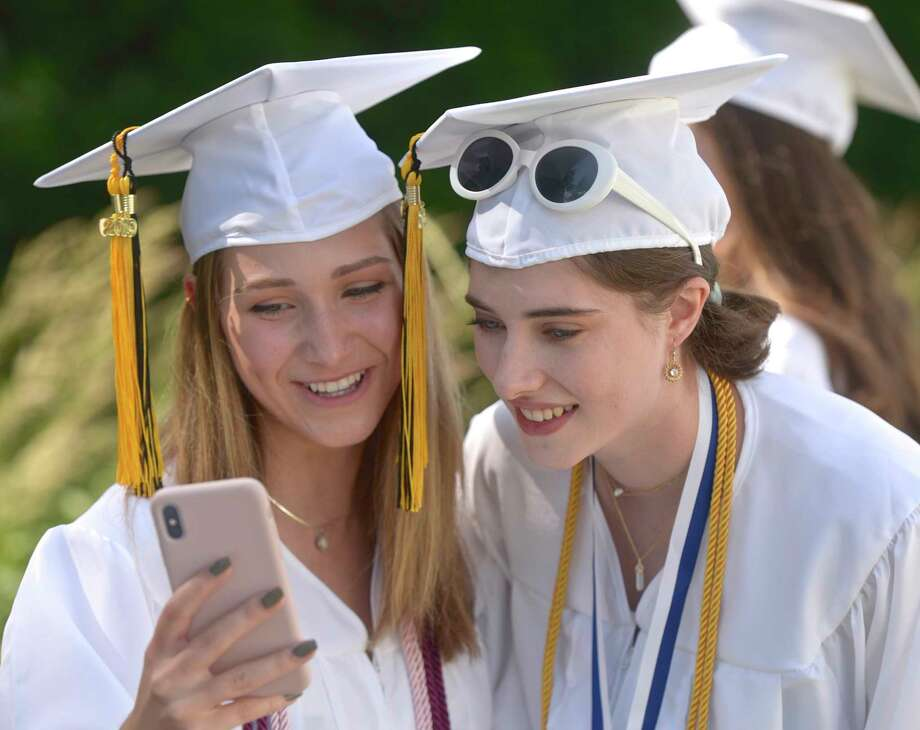 Heidi Lee Hoffman, left, and Alizabeth M. Neville admire a photo they just took before the Joel Barlow High School 2019 Commencement Ceremony, Wednesday June 12, 2019, at The O'Neill Center at Western Connecticut State University, Danbury, Conn. Photo: H John Voorhees III, Hearst Connecticut Media / The News-Times