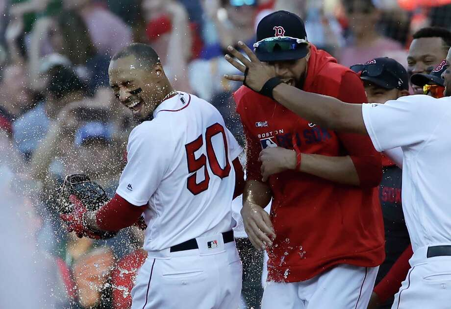 Boston Red Sox's Mookie Betts (50) is doused by teammates after drawing a game-ending, bases-loaded walk that gave the team a 4-3 win over the Texas Rangers in a baseball game at Fenway Park, Wednesday, June 12, 2019, in Boston. (AP Photo/Elise Amendola) Photo: Elise Amendola / Copyright 2019 The Associated Press. All rights reserved