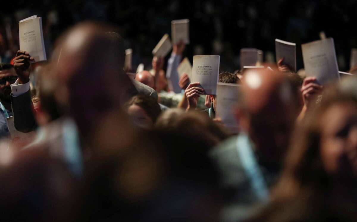 Thousands of people hold up copies of a training handbook related to sexual abuse within Southern Baptist churches during a speech by SBC President J. D. Greear on the second day of the SBC's annual meeting on Wednesday, June 12, 2019, in Birmingham.