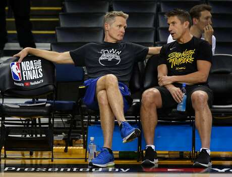 Head coach Steve Kerr confers with director of sports medicine and performance Rick Celebrini during a Golden State Warriors practice at Oracle Arena in Oakland, Calif. on Wednesday, June 12, 2019 before Thursday's Game 6 of the NBA Finals against the Toronto Raptors.