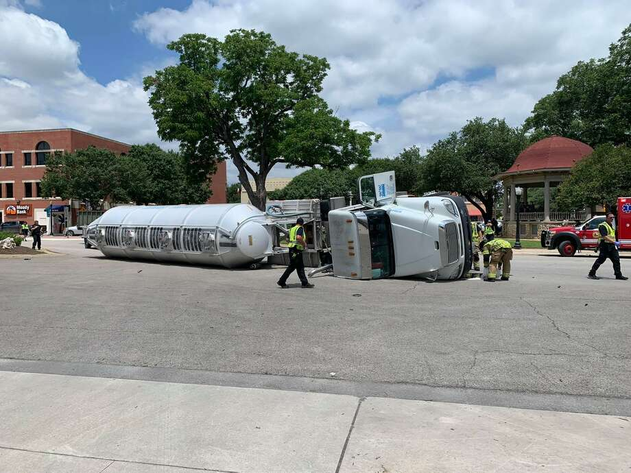 Police and firefighters inspect an 18-wheeler filled with about 50,000 pounds of flour that rolled over at Main Plaza in New Braunfels on Wednesday, June 12, 2019. Photo: Courtesy / New Braunfels Police Department.
