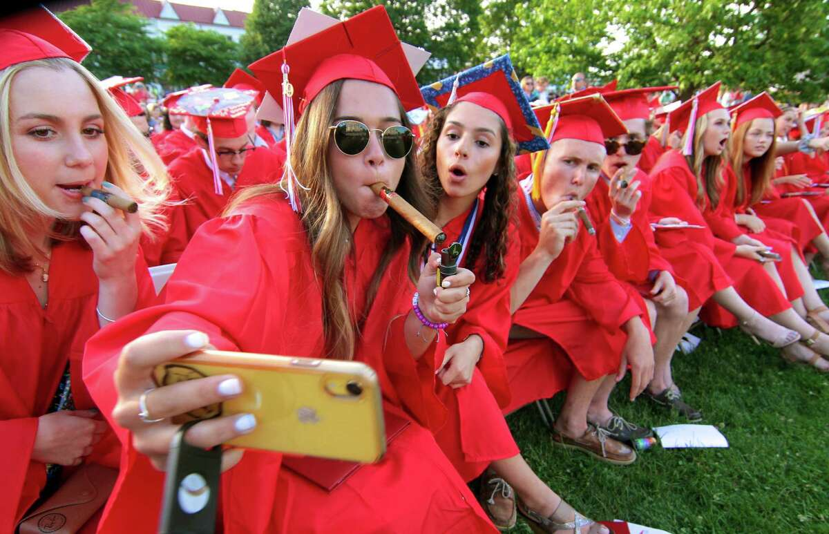 Graduate Emma Luhn takes a selfie as she lights up a cigar with her friends during Branford High School's Graduation Ceremony on the Branford Green in downtown Brandford, Conn., on Wednesday June 12, 2019.