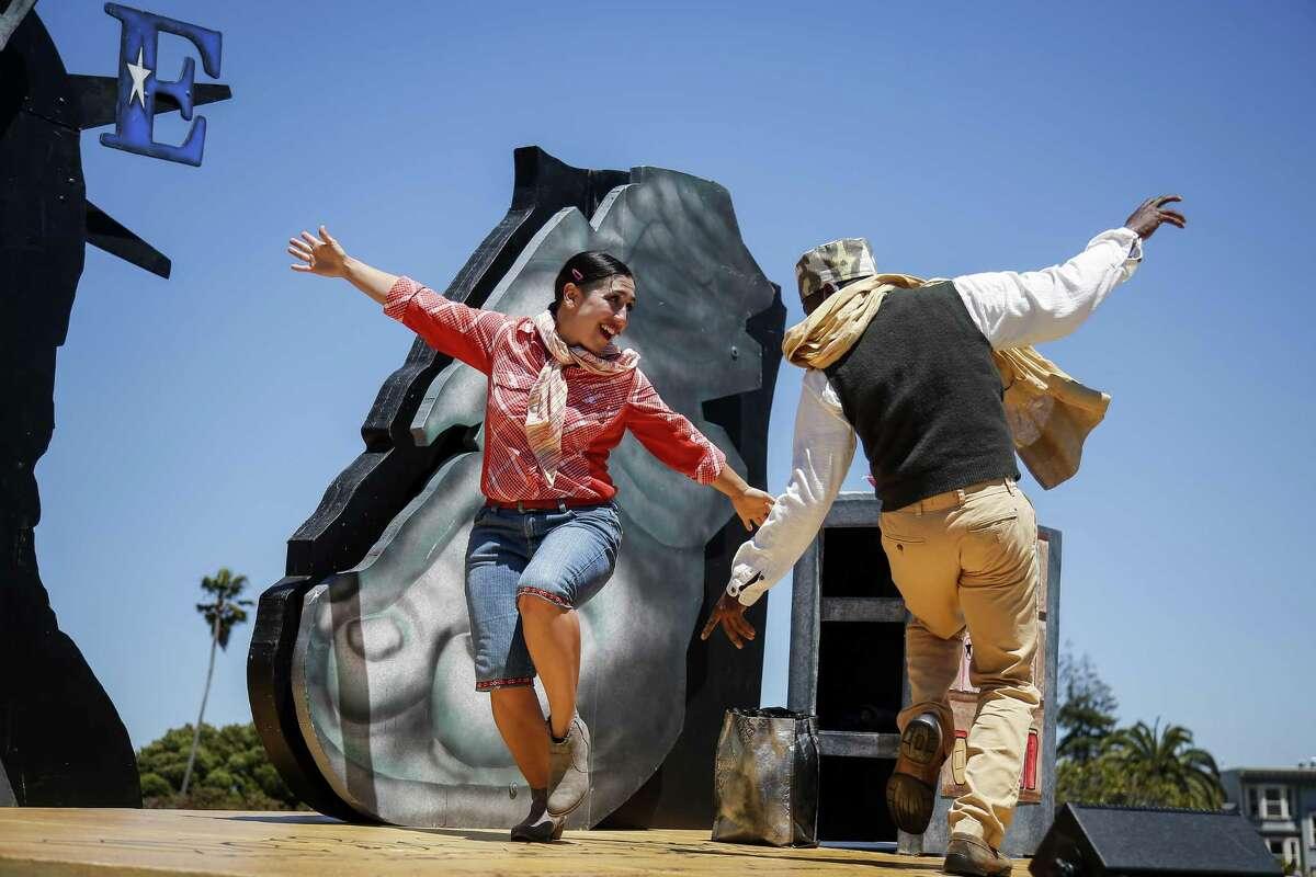 """ARCHIVO- Marilet Martinez, izquierda, interpreta a una mujer indocumentada de México, y Rotimi Agbabiaka, derecha, interpreta a un inmigrante de Somalia, bailan para San Francisco Mime Troupe durante el estreno de """"Walls"""" (Muros) escrita por Michael Gene Sullivan y dirigida por Edris Cooper-Anifowoshe en Mission Delores Park en San Francisco, el 4 de julio de 2017."""
