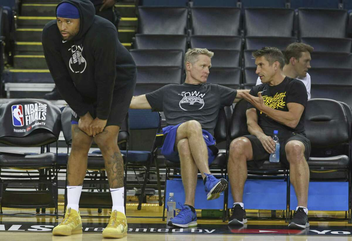 Head coach Steve Kerr confers with director of sports medicine and performance Rick Celebrini as DeMarcus Cousins works out during a Golden State Warriors practice at Oracle Arena in Oakland, Calif. on Wednesday, June 12, 2019 before Thursday's Game 6 of the NBA Finals against the Toronto Raptors.
