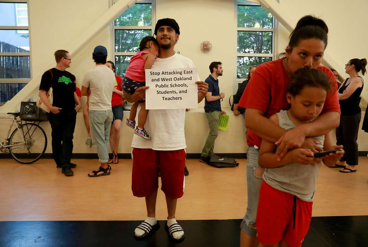 Jaliah Cepeda (center left), 1.5 years old, Jesus Cepeda (center right), Natalie Carrillo (second from right), and Jayden Carrillo, 7, attend a Oakland Unified School District meeting in the Great Room at the LaEscuelita Center in Oakland, Calif., on Wednesday, June 12, 2019. Darnisha Wright, a kindergarten teacher at Markham Elementary in East Oakland, was choked by OUSD board member Jumoke Hinton Hodge during the teacher's strike in March, an altercation that was caught on video, which went viral. In April, less than a month after the incident and shortly after Wright said she would file charges, she received a letter from the principal of her school that terminated her employment.