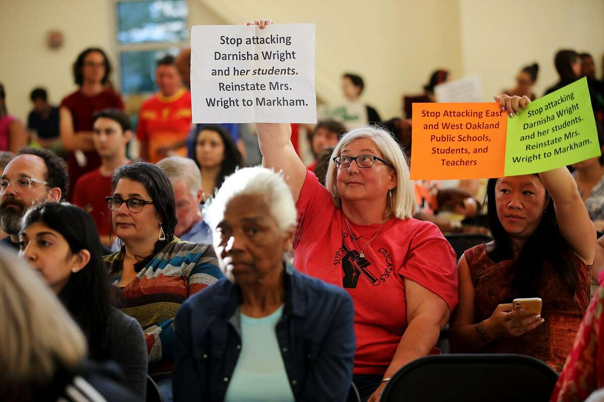 Lisa Hiltbrand (second from right), 2011 Oakland Teacher of the Year, and Cory Jong, hold signs as they attend a Oakland Unified School District meeting in the Great Room at the LaEscuelita Center in Oakland, Calif., on Wednesday, June 12, 2019. Darnisha Wright, a kindergarten teacher at Markham Elementary in East Oakland, was choked by OUSD board member Jumoke Hinton Hodge during the teacher's strike in March, an altercation that was caught on video, which went viral. In April, less than a month after the incident and shortly after Wright said she would file charges, she received a letter from the principal of her school that terminated her employment.