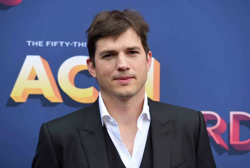 FILE - In this April 15, 2018, file photo, Ashton Kutcher arrives at the 53rd annual Academy of Country Music Awards at the MGM Grand Garden Arena in Las Vegas. The News and Sentinel reports Parkersburg High School Principal Kenny DeMoss was suspended Tuesday, June 11, 2019 at a Wood County Board of Education meeting. DeMoss apologized for heavily basing his May address on Kutcher's 2013 Nickelodeon Teen Choice Awards speech. He has said he should?ve cited his sources, but the ideas were his own. (Photo by Jordan Strauss/Invision/AP, File)