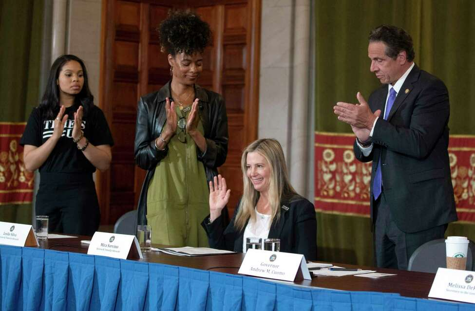 New York Governor Andrew Cuomo, right, applauds Oscar-winning actress Mira Sorvino as she joined Times's Up advocates speaking out about sexual assault at the State Capitol in Albany, N.Y., Tuesday, June 12, 2019. Sorvino has revealed that she's a survivor of date rape in an attempt to lend her voice to a push for stronger sexual assault laws in New York. (Mike Groll/Office of Governor Andrew M. Cuomo via AP)