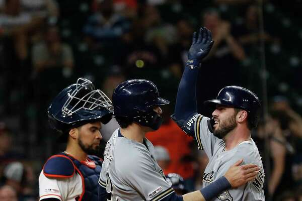 Milwaukee Brewers Mike Moustakas (11) hugs Christian Yelich (22) after he hit a two-run homer during the fourteenth inning of an MLB baseball game at Minute Maid Park, Wednesday, June 12, 2019.