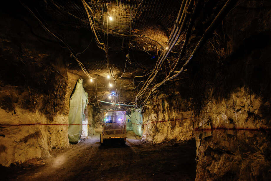 Lights illuminate a mining truck moving through an underground tunnel at a gold mine. Photo: Bloomberg Photo By Waldo Swiegers / Bloomberg