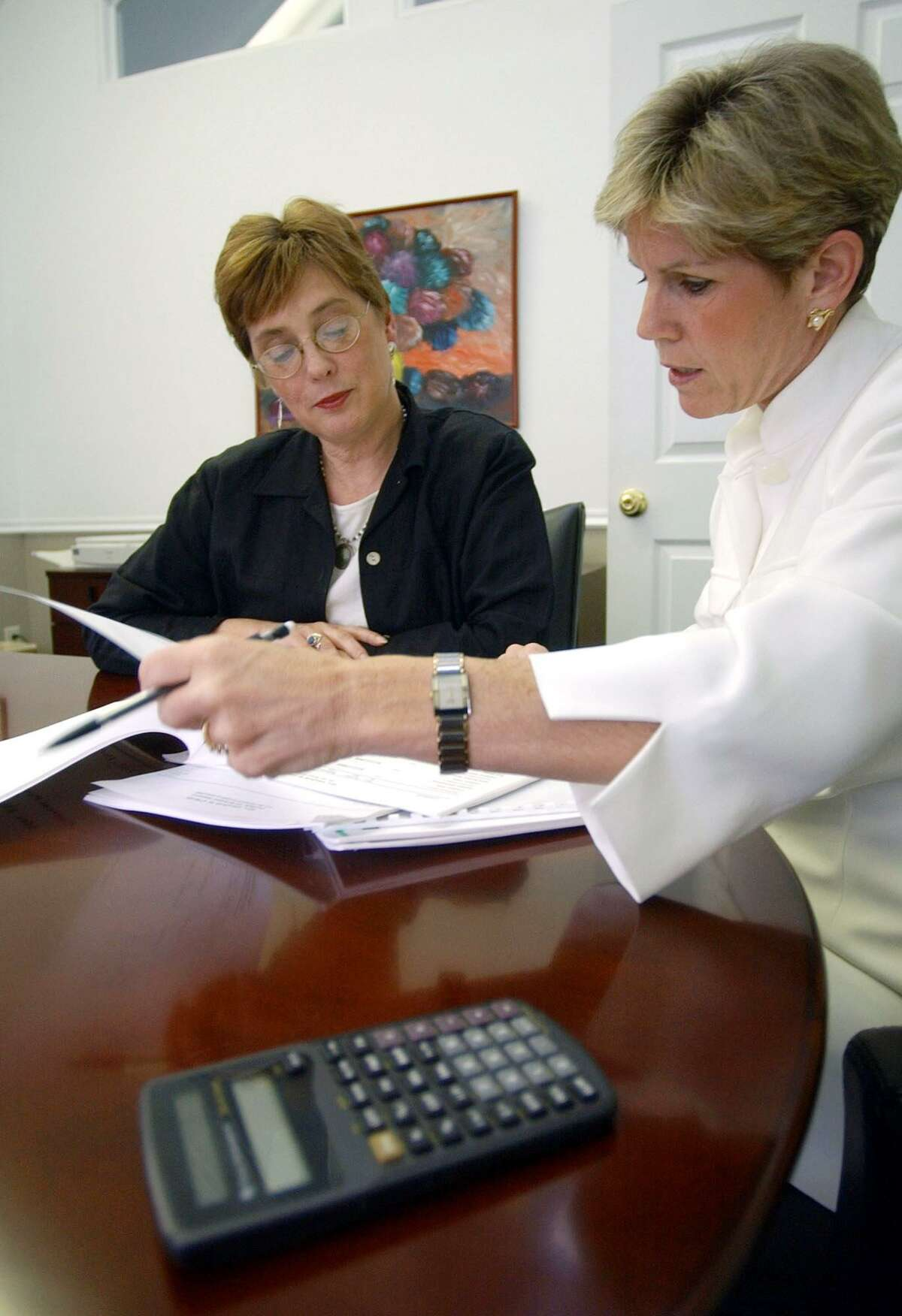 A certified financial planner reviews the portfolio of her client, a 60-year-old mother of three.