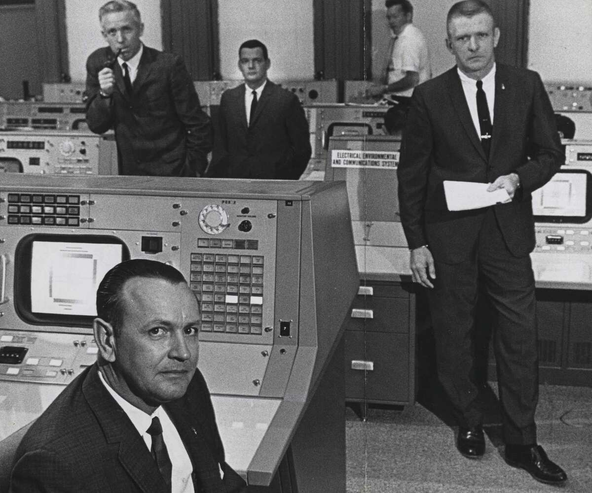 Shown in this June 1965 photo are NASA flight director Christopher Kraft, foreground, and (L-R, in suits) John D. Hodge, chief of the flight control division; Glynn Lunney, flight director at Cape Kennedy during launch phase only; and Gene Kranz, who spells Kraft as flight director.