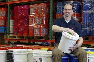 Pastor Scott Moore, executive director of the Mission Center, a ministry of the Texas Annual Conference of the United Methodist Church, poses for a portrait atop a portion of the organization's more than 1,400 flood buckets filled with items from soap to trash bags and sponges to help residents clean up their homes following a natural disaster. Moore, a former police office and frontline responder when Hurricane Rita hit Beaumont in September 2005, has lead the center since it opened along Loop 336 East in 2016.