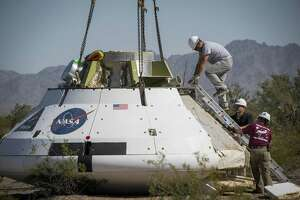 A model of NASA's Orion spacecraft is picked up by a crane after being dropped from a C-17 to test the Capsule Parachute Assembly System at the U.S. Army Yuma Proving Ground on Wednesday, April 23, 2014, in Yuma. For the test, which is the 13th of 17 planned tests, the test vehicle was dropped from 13,000 feet to simulate conditions that the parachutes would see during ascent or pad abort.