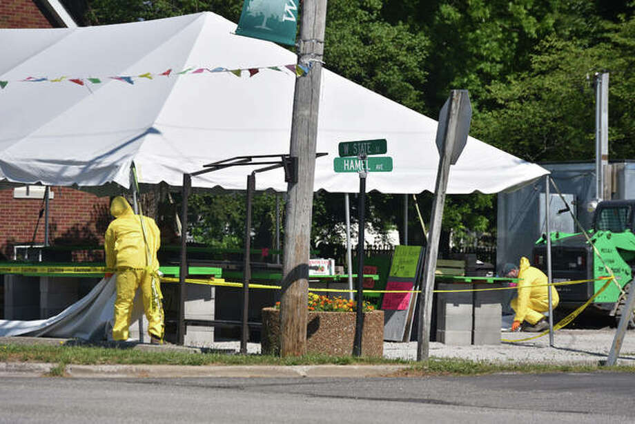 Traffic slowed to take a look at the Hamel produce stand where Illinois Environmental Protection Agency workers in protective suits and respirators removed presumably contaminated product from the tent. Photo: Melissa Pitts | The Intelligencer