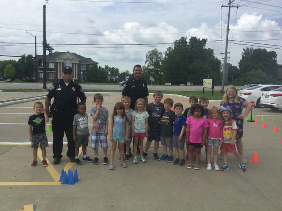 Lt. White and Sgt. Jones pose with the La Petite students and their teacher during a bike safety rodeo.