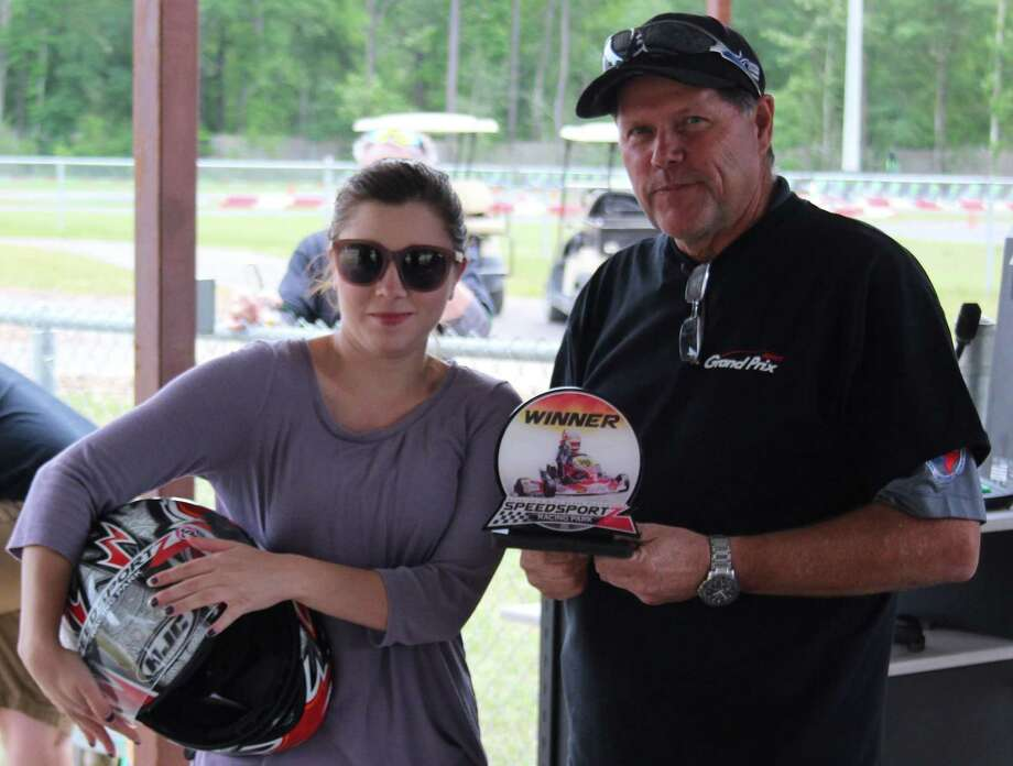 Lauren Bullock (left) is presented with a trophy by Greater East Montgomery County Chamber President Rick Hatcher (right) at the second annual Grand Prix held on April 20. Photo: Jacob McAdams / HCN