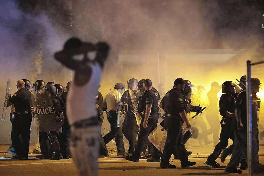 Police retreat under a cloud of tear gas as protesters disperse from the scene of a standoff after Frayser community residents took to the streets in anger against the shooting of a youth by U.S. Marshals earlier in the evening, Wednesday, June 12, 2019, in Memphis, Tenn. (Jim Weber/Daily Memphian via AP) Photo: Jim Weber, Associated Press