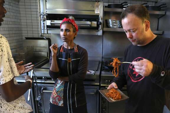 Owner/creator Azalina Eusope (middle) talks with general manager DeHandre Weaver (left) and business partner Tim Benson (right) as they test out new pans for the first time at Mahila on Wednesday, June 12, 2019, in San Francisco, Calif.  Mahila, the first full-service Mamak (Indian Muslim) restaurant to ever open in San Francisco.