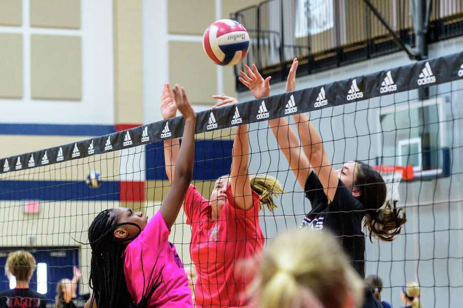 Kennedy Jones, 12, (left) hits the ball over the net as Addison Moss, 12 and Gracie Williams, 13, try to block the ball during a volleyball camp at Dawson High School. (Photos: Kim Christensen) Photo: Kim Christensen, Photographer / Kim Christensen / Copyright Kim Christensen