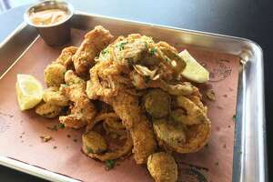 Cajun Debris is a 225 Urban Smoke menu favorite that includes fried catfish, pickles, jalapeños and onion rings in a mash.