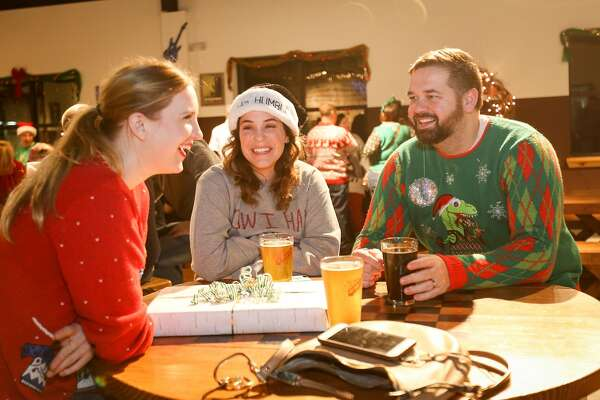 The Woodlands residents Lindsey Schulz, left, and Sarah and Jeff Wilkins chat while donning ugly Christmas sweaters for a contest during the Southern Star Christmas Party on Friday, Dec. 22, 2017, at the Southern Star Brewing Company in Conroe.