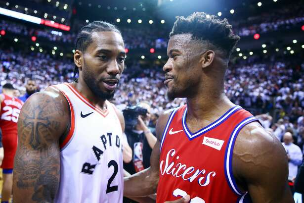 TORONTO, ON - MAY 12: Kawhi Leonard #2 of the Toronto Raptors speaks with Jimmy Butler #23 of the Philadelphia 76ers after sinking a buzzer beater to win Game Seven of the second round of the 2019 NBA Playoffs at Scotiabank Arena on May 12, 2019 in Toronto, Canada. NOTE TO USER: User expressly acknowledges and agrees that, by downloading and or using this photograph, User is consenting to the terms and conditions of the Getty Images License Agreement. (Photo by Vaughn Ridley/Getty Images)