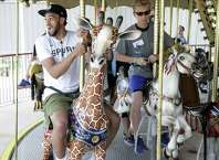 Spurs guard Derrick White gets on the tallest seat on the merry-go-round as he visits Morgan's Wonderland with a group of special needs children on June 12, 2019.