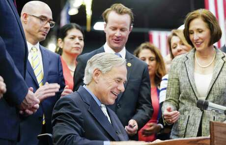 Texas Gov. Greg Abbott laughs after signing a Harvey-related measure at Gallery Furniture on Thursday, June 13, 2019 in Houston.