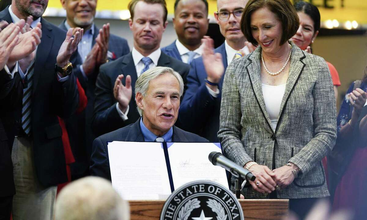 Texas Gov. Greg Abbott holds up a bill after signing it during a ceremony at Gallery Furniture on Thursday, June 13, 2019 in Houston.