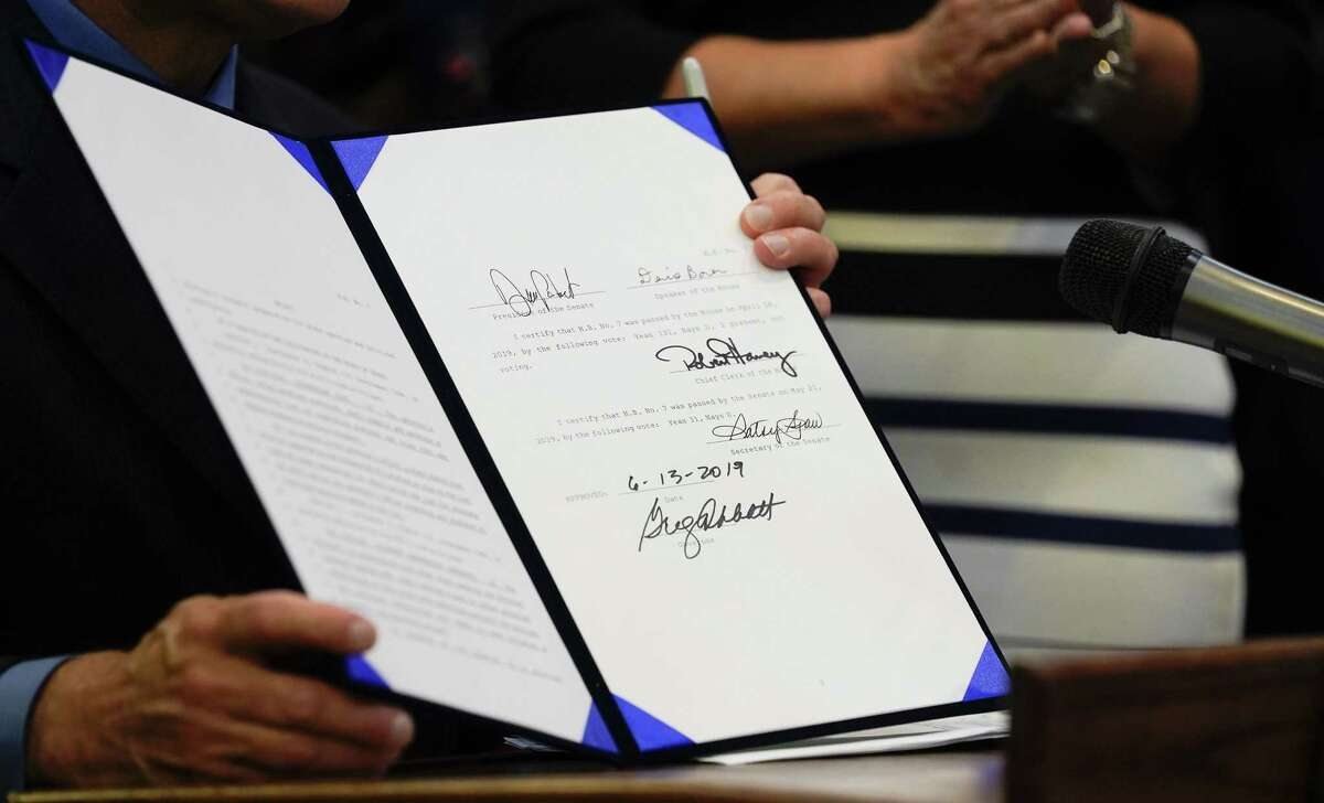 Texas Gov. Greg Abbott holds a bill after signing the Harvey-related measure at Gallery Furniture on Thursday, June 13, 2019 in Houston.