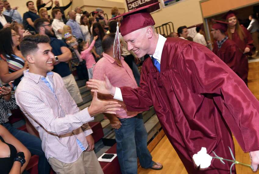 Colby Cusano (left) greets Shamus Meehan as he enters the gymnasium for the North Haven High School commencement on June 13, 2019.